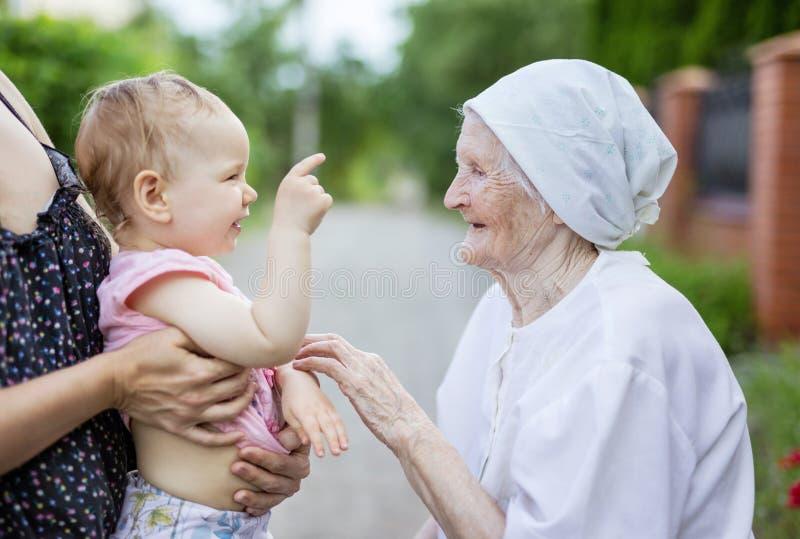 Nettes Kleinkindmädchen, das mit ihrer Urgroßmutter spielt Geerntete Ansicht der Mutterholdingtochter stockfotos