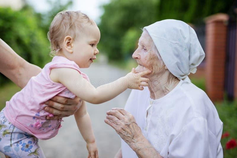 Nettes Kleinkindmädchen, das mit ihrer Urgroßmutter spielt und ihr Gesicht berührt lizenzfreie stockfotografie
