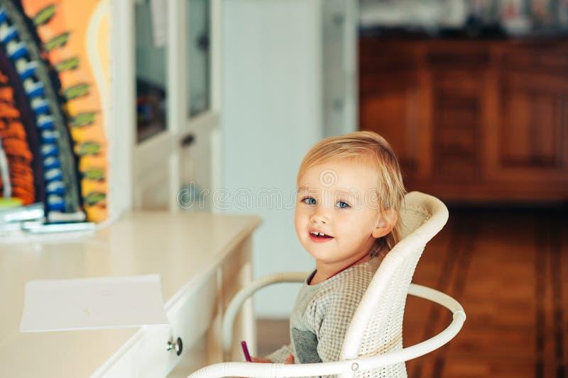 Nettes Kleinkindmädchen, das am Schreibtisch sitzt stockfotos