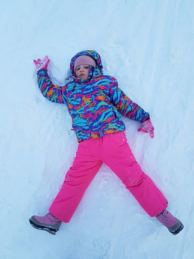 Nettes Kleinkindmädchen in der warmen Skisportklage, die draußen Schneeengel macht Scherzen Sie Haben des Spaßes, der auf Schneew stockfotografie
