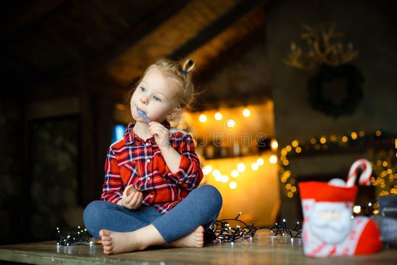 Nettes Kleinkindmädchen, welches das Schokoladenei sitzt in einem Jagdhaus verziert für Weihnachten isst Das Konzept eines Weihna stockbilder