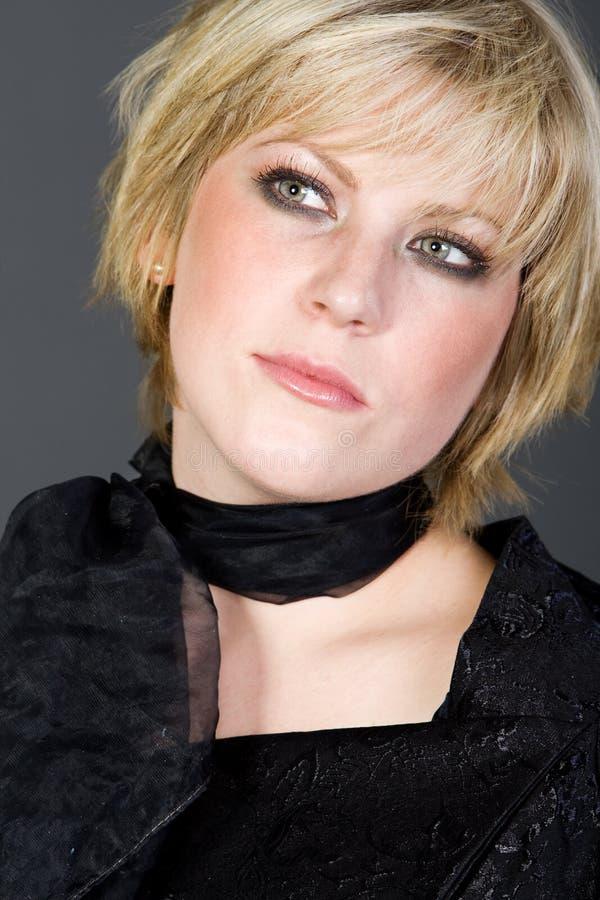 Nettes kurzes blondes behaartes Mädchen gegen Grau lizenzfreies stockfoto