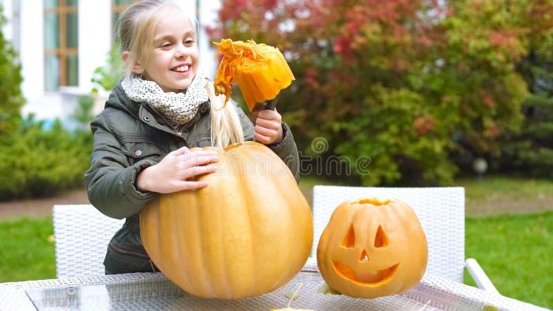 Nettes lächelndes Mädchen, das Kürbis Jack, den Spaß habend schnitzt und genießen Halloween-Vorabend lizenzfreie stockfotografie
