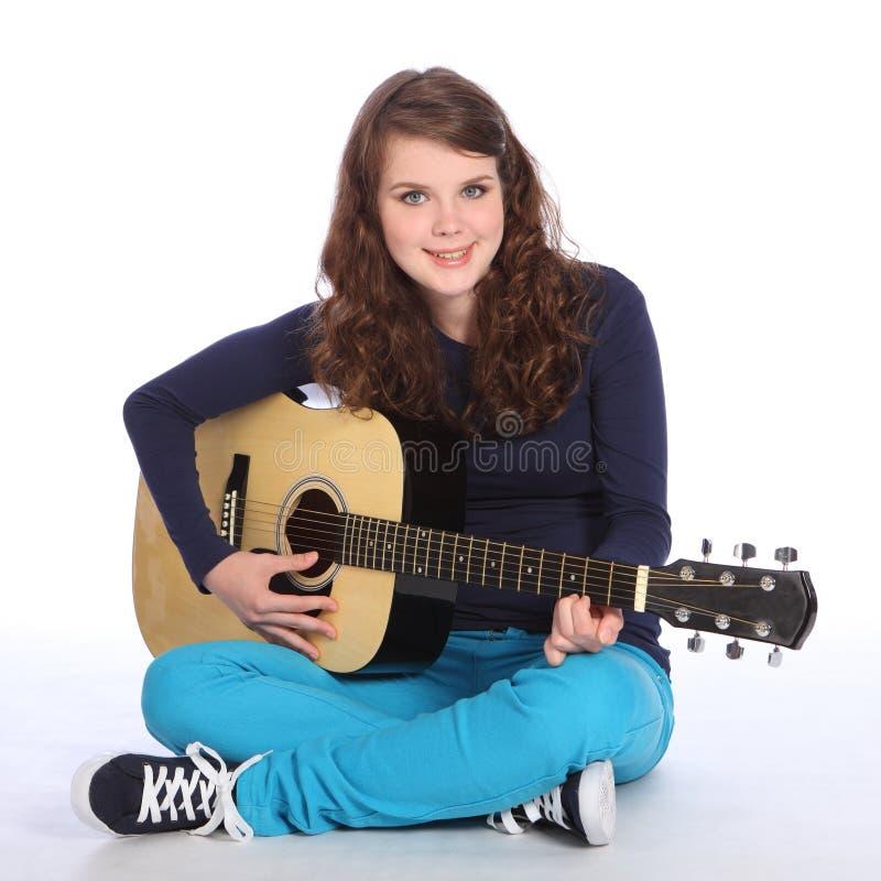 Nettes Lächeln durch Jugendlichmädchen auf Akustikgitarre lizenzfreie stockfotos