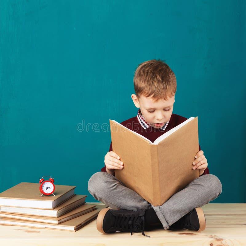 Nettes lächeln wenig Schuljunge, der auf einem Schreibtisch gegen tur sitzt lizenzfreies stockfoto