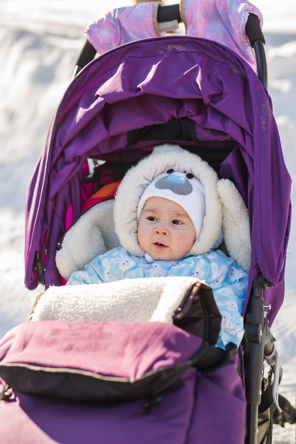 Nettes lächelndes Baby, das im Spaziergänger an einem kalten Wintertag sitzt stockbilder