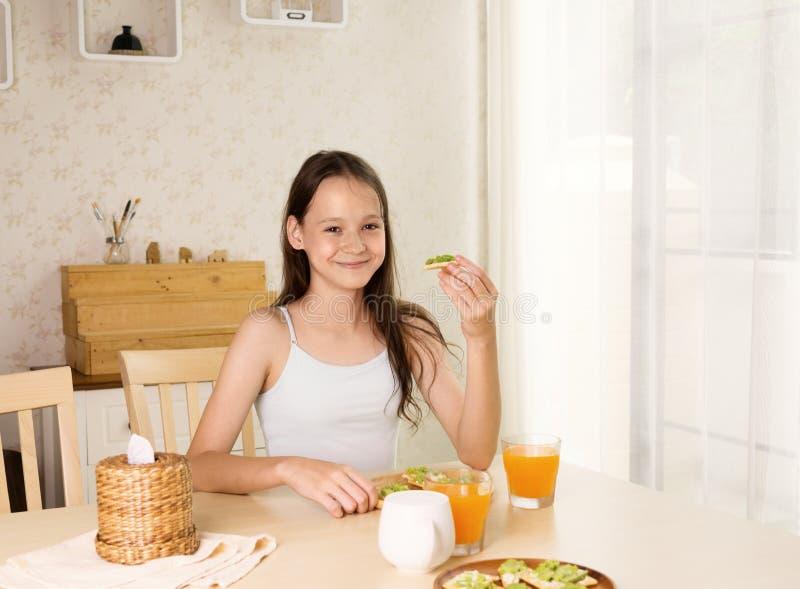 Nettes lächelndes jugendliches Mädchen, das gesundes frühstückt: Avocadosandwich und Orangensaft Gesundes Lebensstilkonzept, vege stockbild