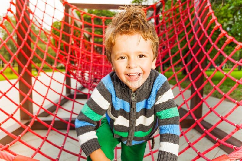 Nettes lächelndes Kind auf rotem Gitter des Spielplatzes stockfotografie