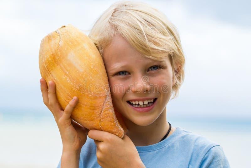 Nettes, lächelndes Kind, das Ballenpreßoberteil zum Ohr hält stockbild