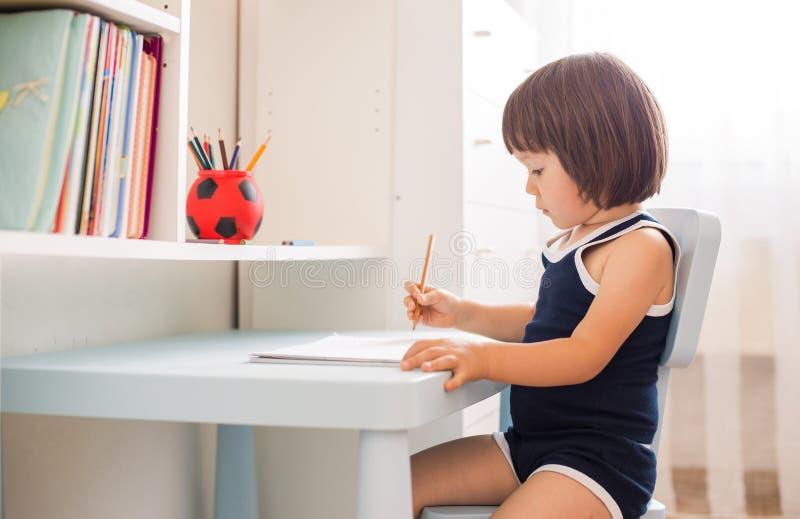 Nettes lächelndes Kind, das Hausarbeit, Färbungsseiten, Schreiben und Malerei tut lizenzfreie stockfotos