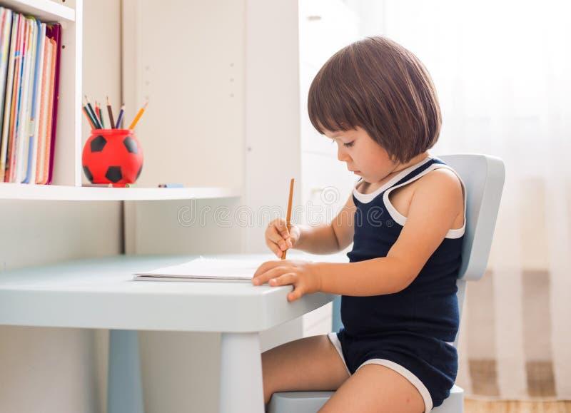 Nettes lächelndes Kind, das Hausarbeit, Färbungsseiten, Schreiben und Malerei tut lizenzfreie stockfotografie