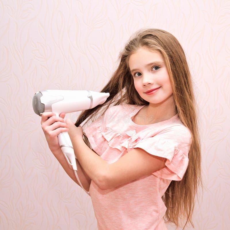 Nettes lächelndes Kind des kleinen Mädchens, das ihr langes Haar mit Haartrockner trocknet lizenzfreies stockfoto