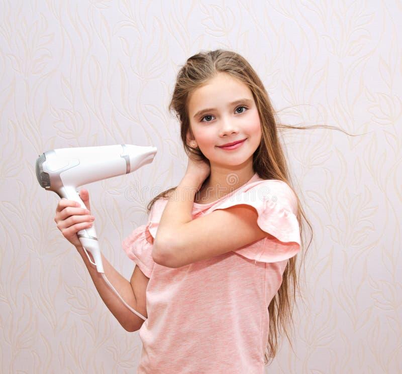 Nettes lächelndes Kind des kleinen Mädchens, das ihr langes Haar mit Haartrockner trocknet lizenzfreies stockbild
