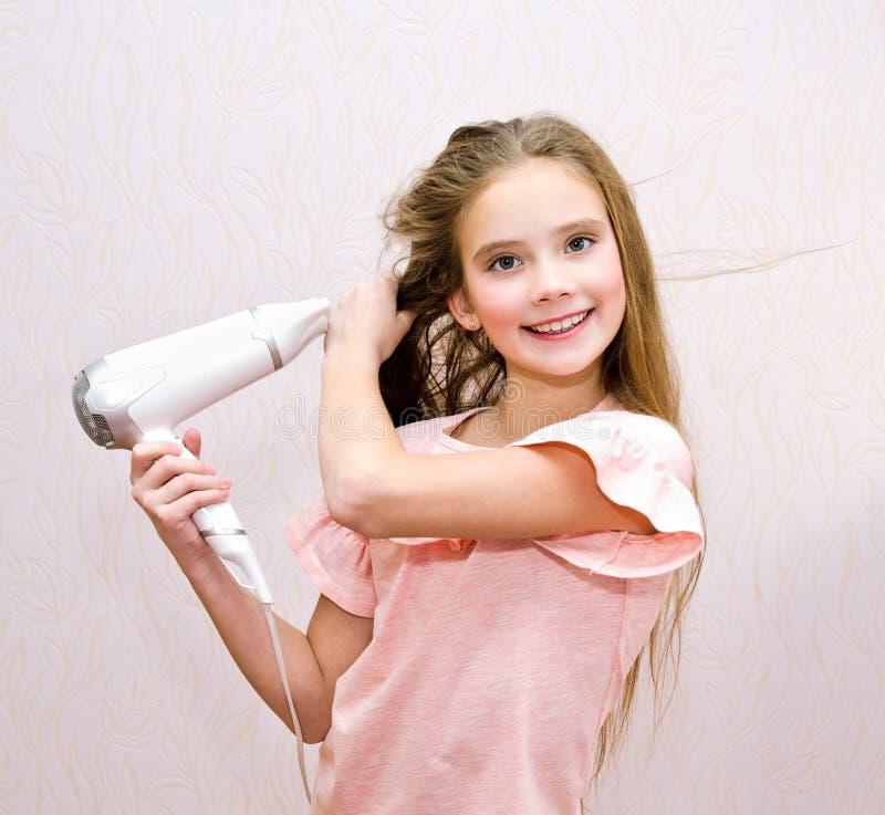 Nettes lächelndes Kind des kleinen Mädchens, das ihr langes Haar mit Haartrockner trocknet lizenzfreie stockbilder