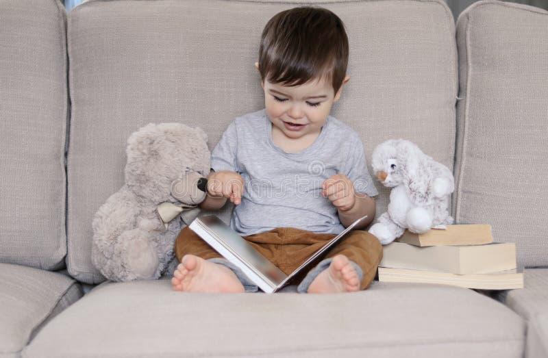 Nettes lächelndes kleines Babylesebuch, das zu Hause auf Sofa mit Teddybärspielzeug und -Häschen sitzt stockbilder