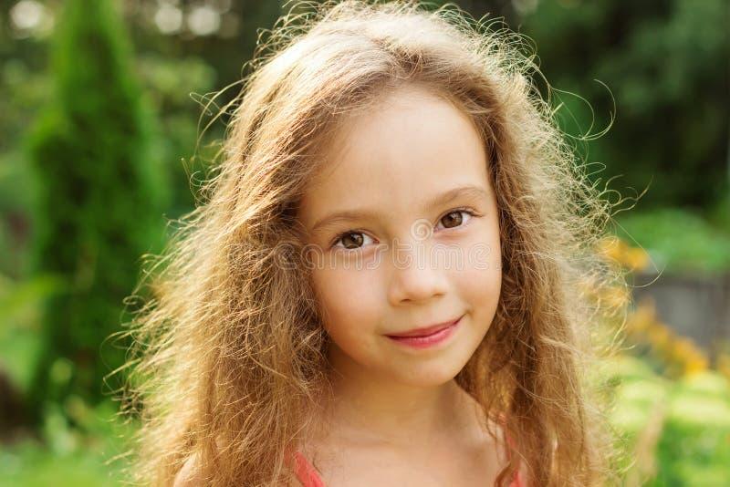 Nettes lächelndes kleines Mädchen auf Hintergrund des Stadtparks am Sommer stockbild