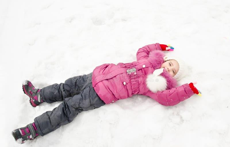 Nettes lächelndes kleines Mädchen, das auf Schnee am Wintertag liegt stockfoto