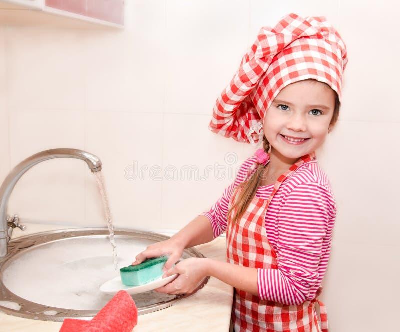 Nettes lächelndes kleines Mädchen, das die Teller wäscht lizenzfreies stockbild