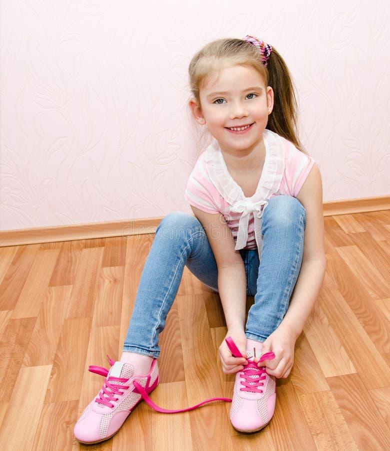 Nettes lächelndes kleines Mädchen, das ihre Schuhe bindet lizenzfreies stockbild