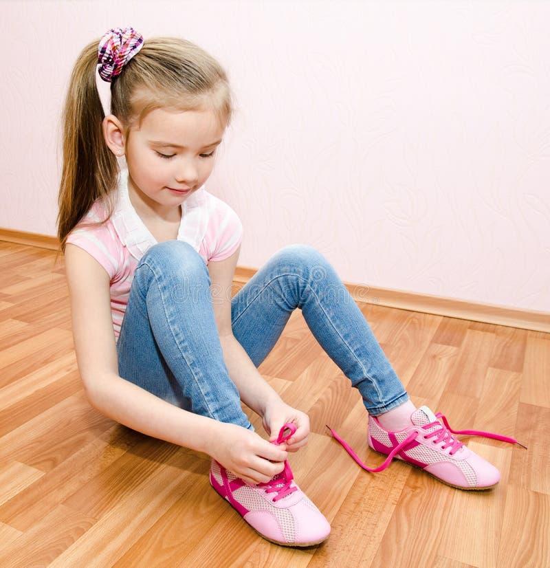 Nettes lächelndes kleines Mädchen, das ihre Schuhe bindet stockbilder