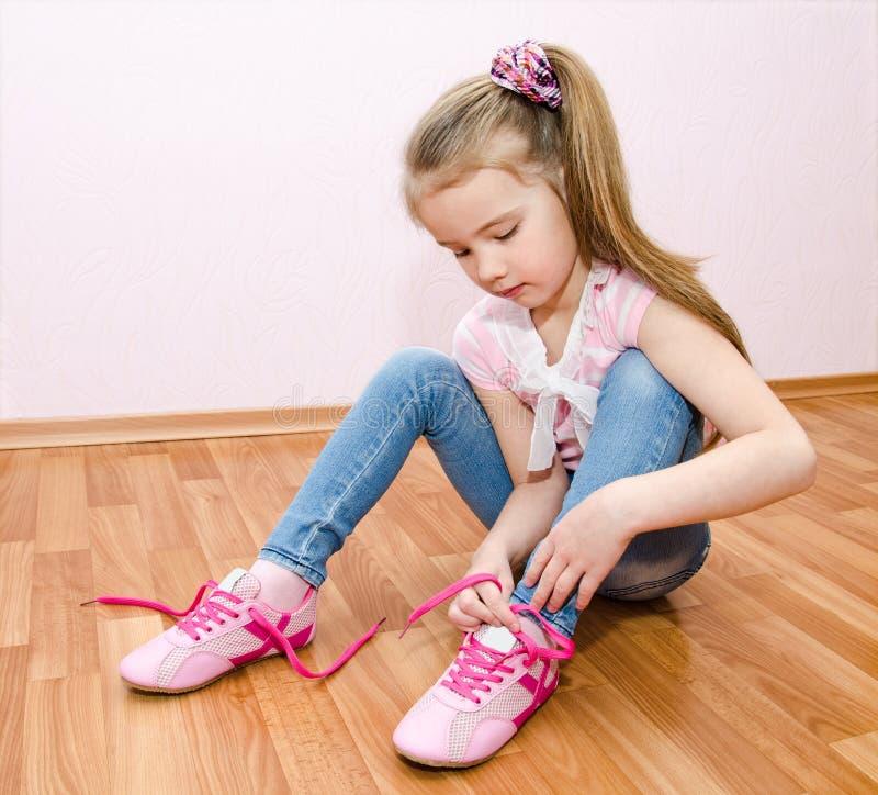 Nettes lächelndes kleines Mädchen, das ihre Schuhe bindet lizenzfreies stockfoto