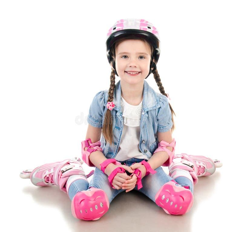 Nettes lächelndes kleines Mädchen in den rosa Rollschuhen stockfotografie
