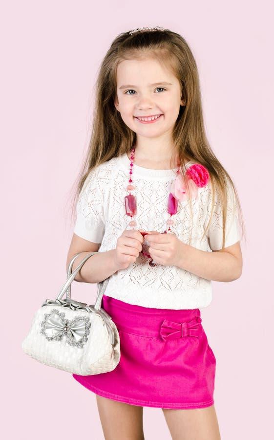 Nettes lächelndes kleines Mädchen im Rock mit Tasche und Perlen stockfotografie