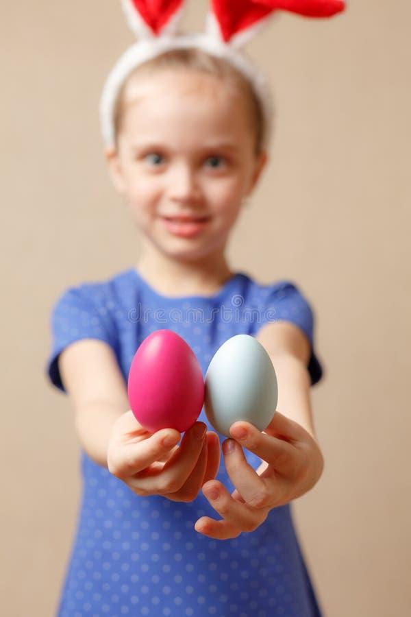 Nettes lächelndes kleines Mädchen mit bunten Ostereiern Fröhliche Ostern Selektiver Fokus lizenzfreie stockfotografie