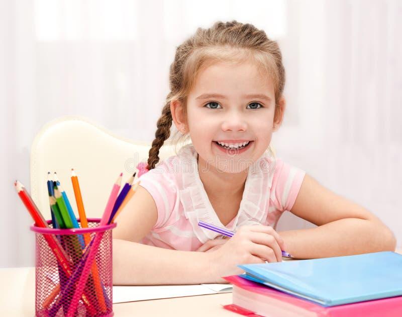 Nettes lächelndes kleines Mädchen schreibt am Schreibtisch stockfotos