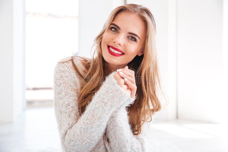Nettes lächelndes Mädchen, das roten Lippenstift und weiße Strickjacke trägt stockfotografie