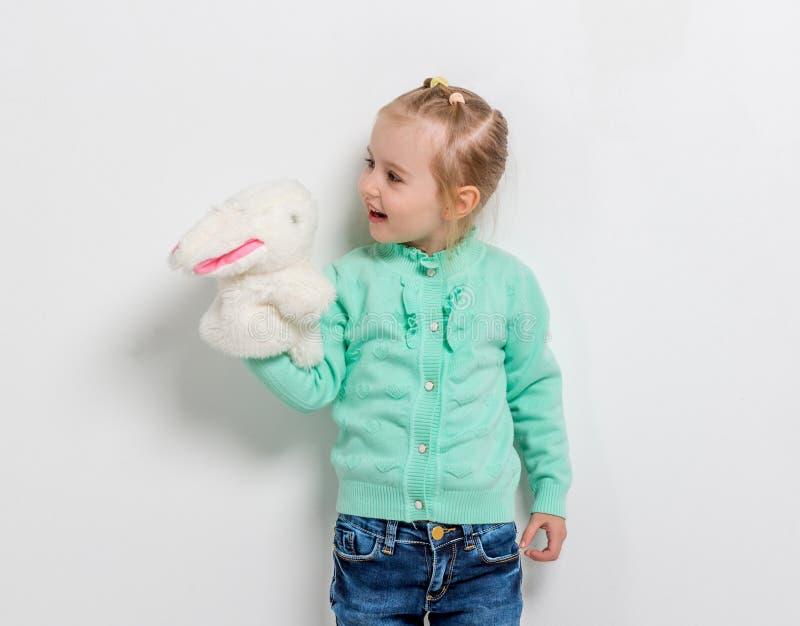 Nettes lächelndes Mädchen, das Spielzeughasen spielt stockfotografie