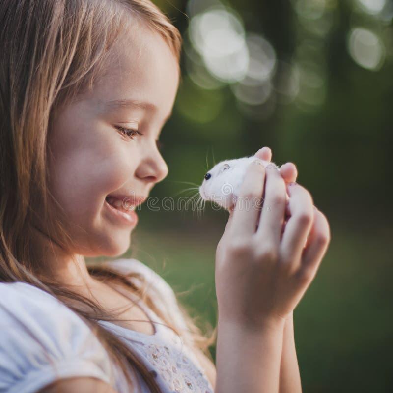 Nettes lächelndes Mädchen, das weißen Hamster - Retro- Blick hält stockbilder