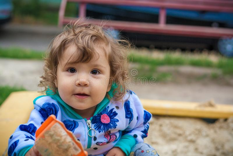 Nettes lächelndes Spielen des kleinen Mädchens im Sandkasten stockfotos