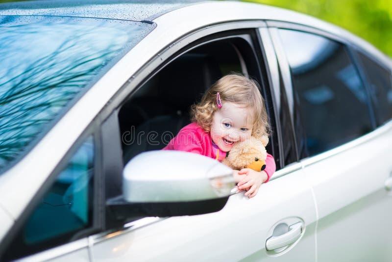 Nettes lachendes Kleinkindmädchen im Auto mit einem Teddybären stockfotografie