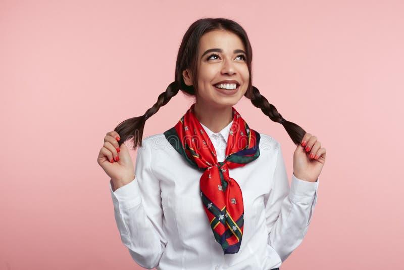 Nettes Latina weiblich mit hellem weißem Hemd des Lächelns, des Tragens und stilvollen dem Schal, ihre Pferdeschwänze gegen rosa  stockfoto