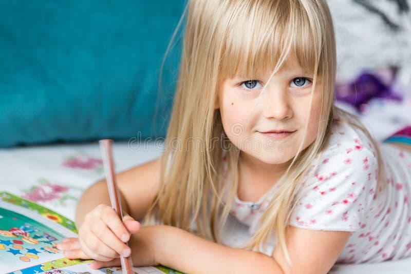 Nettes liitle blondes Mädchen, das auf einem Bett liegt und Hausarbeit macht lizenzfreie stockbilder