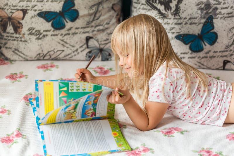 Nettes liitle blondes Mädchen, das auf einem Bett liegt und hometasks im Arbeitsbuch mit einem Bleistift in einer Hand macht lizenzfreies stockbild