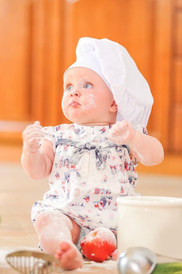 Nettes liitle Mädchen in Chef ` s Hut, der auf dem Küchenbodenboden sitzt stockfotografie