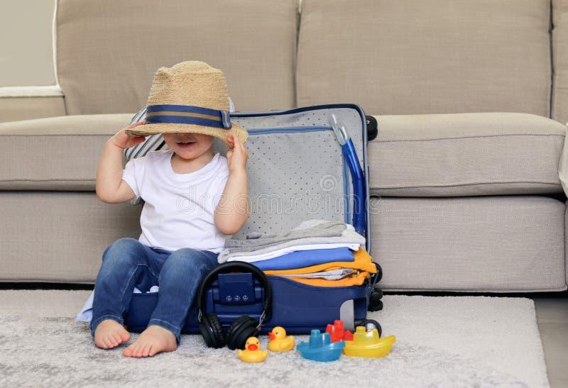 Nettes lustiges kleines Baby, das im blauen Koffer mit Hut auf seinen Augen, voll verpackt für Ferien der Kleidung bereit zum Rei stockfotografie