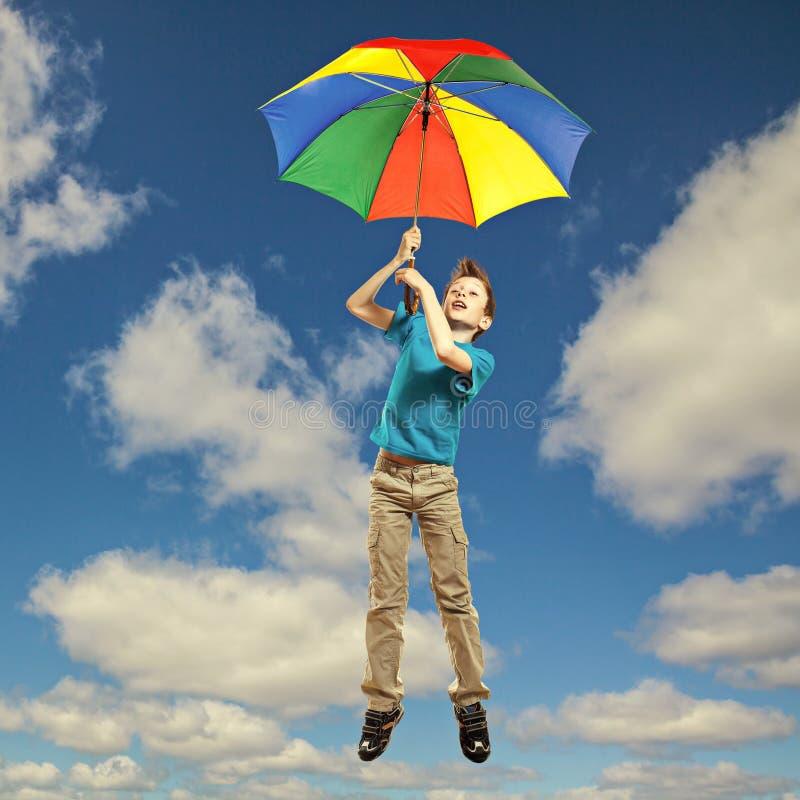 Nettes lustiges kleines Kind in T-Shirt Fliegen im Himmel mit Regenschirm stockfoto