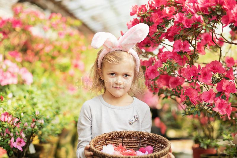 Nettes lustiges Mädchen mit den Osterhasenohren am Garten Junges Küken in Wanne, 2 malte Eier und Blumen Lachendes Kind an der Os lizenzfreies stockbild
