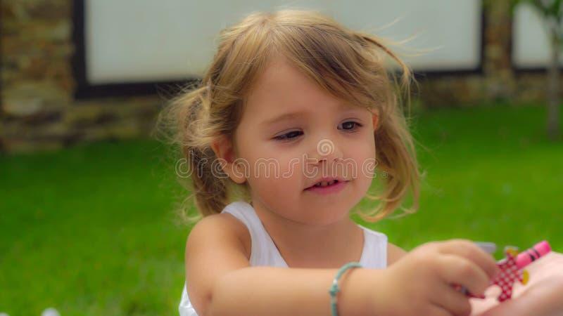 Nettes Mädchen mit dem langen blonden Haar, das im weißen Kleid an sitzt trägt stockfotos