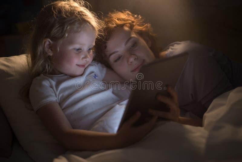 Nettes Mädchen Ablesenebook mit Mutter stockbild