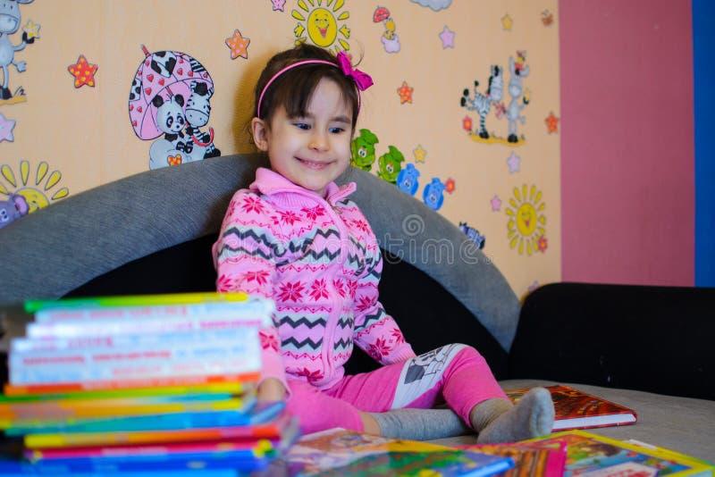 Nettes Mädchen auf dem Hintergrund ihrer Spielwaren mit einem Buch stockfotografie