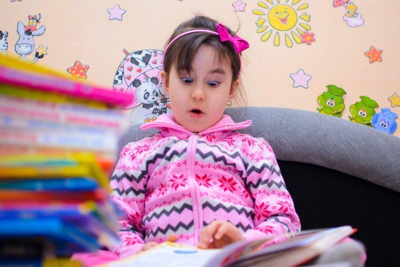 Nettes Mädchen auf dem Hintergrund ihrer Spielwaren mit einem Buch lizenzfreie stockfotos