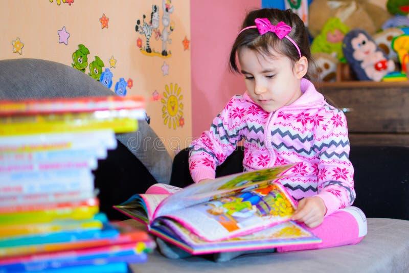 Nettes Mädchen auf dem Hintergrund ihrer Spielwaren mit einem Buch stockbild