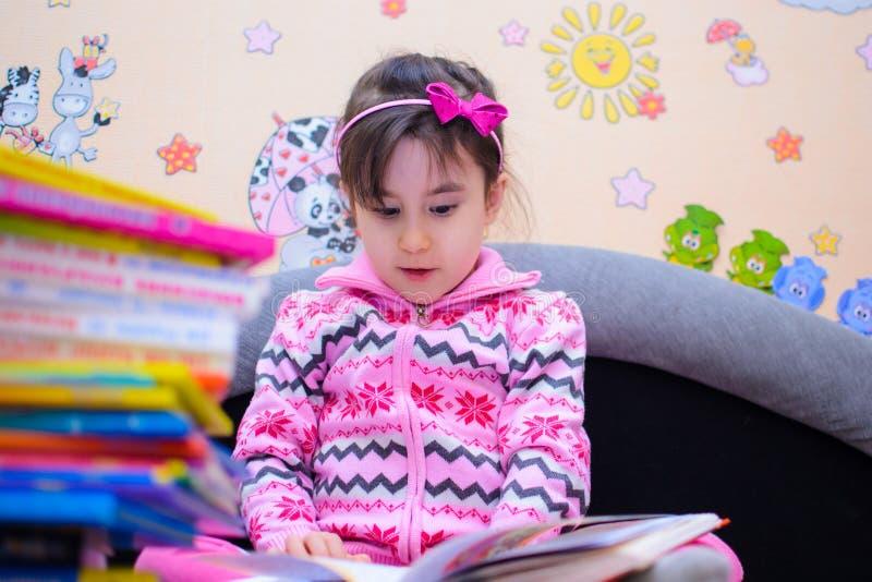 Nettes Mädchen auf dem Hintergrund ihrer Spielwaren mit einem Buch lizenzfreies stockfoto