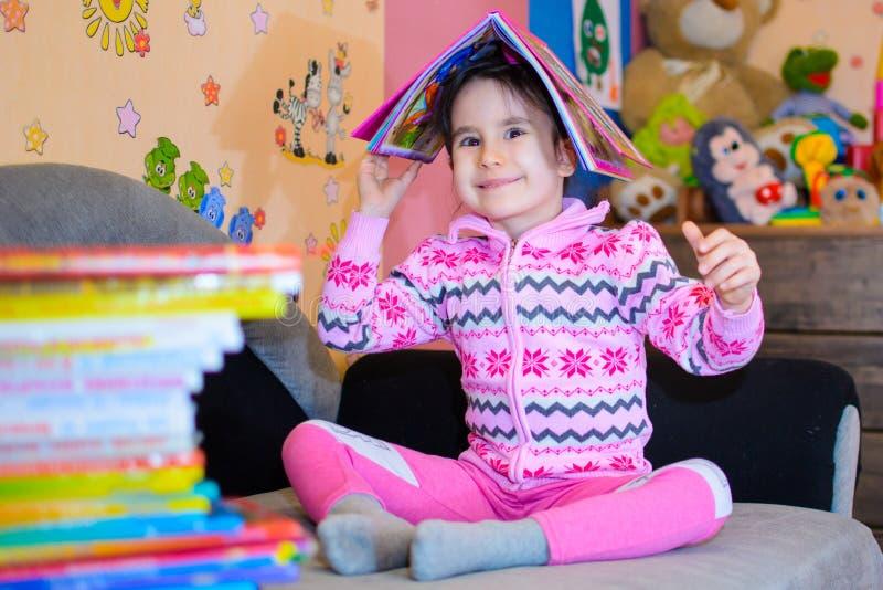 Nettes Mädchen auf dem Hintergrund ihrer Spielwaren mit einem Buch lizenzfreie stockfotografie
