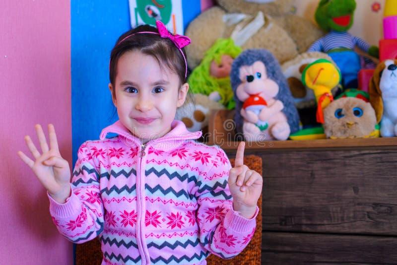 Nettes Mädchen auf dem Hintergrund ihres Spielwarenlächelns lizenzfreies stockbild