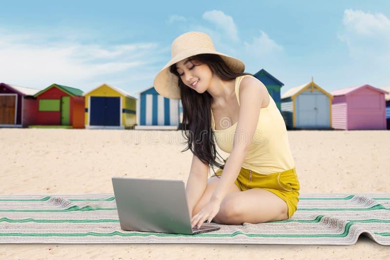 Nettes Mädchen benutzt Notizbuch auf dem Strand lizenzfreies stockfoto